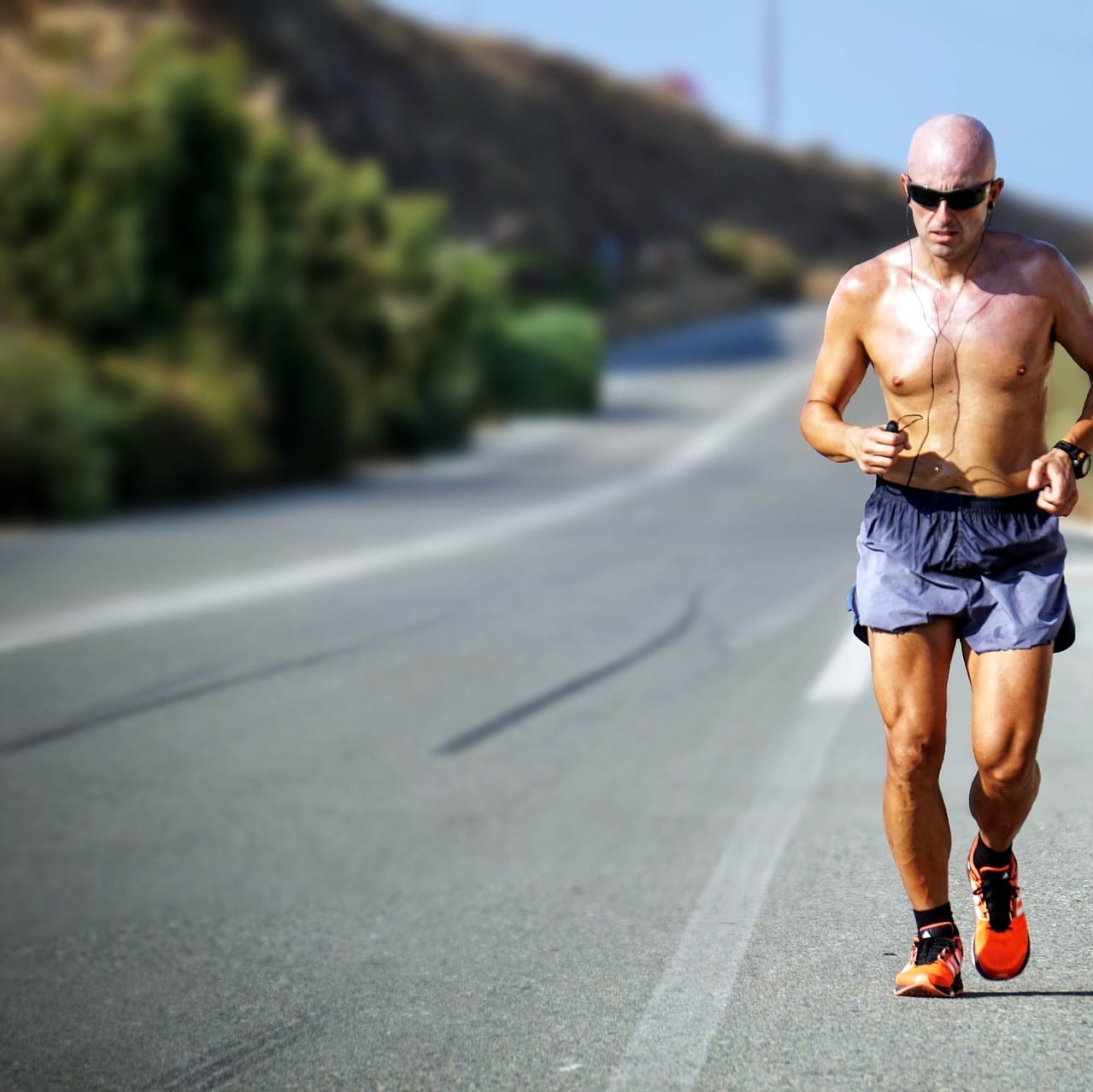 Man running on a road without a shirt