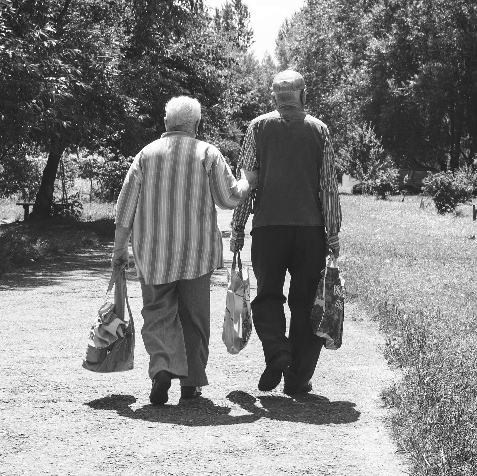 An elderly pair walking and lifting bags