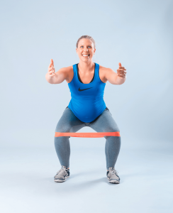 Pregnant women in blue using bands to workouts