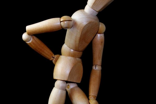A man made of wood standing with back pain